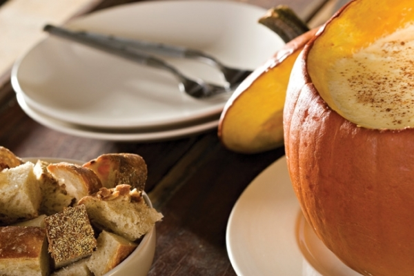 Dip or fondue served from a festive carved pumpkin is a great way to integrate your autumn theme into the menu.|